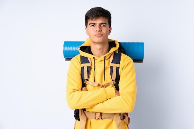 Młody alpinista mężczyzna z dużym plecakiem nad odosobnionym błękitem utrzymuje ręki krzyżować