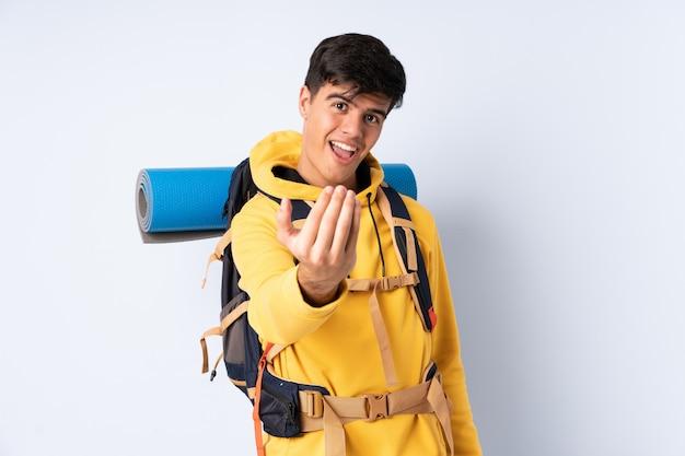 Młody alpinista mężczyzna z dużym plecakiem zaprasza na pojedyncze niebieskie tło