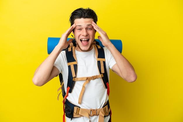 Młody alpinista rosyjski mężczyzna z dużym plecakiem na żółtym tle z wyrazem zaskoczenia
