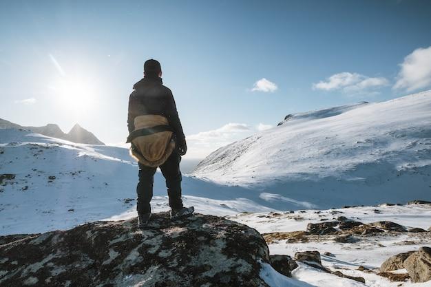 Młody alpinista stojący na zaśnieżonym wzgórzu ze światłem słonecznym świeci na zimę na lofotach, norwegia
