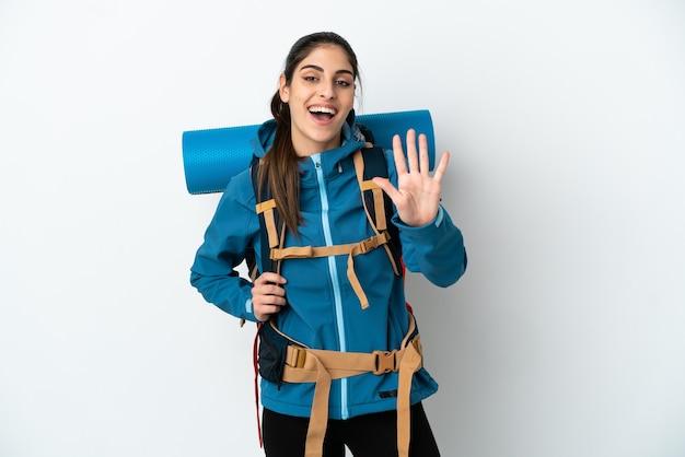 Młody alpinista z dużym plecakiem na białym tle, licząc pięć palcami