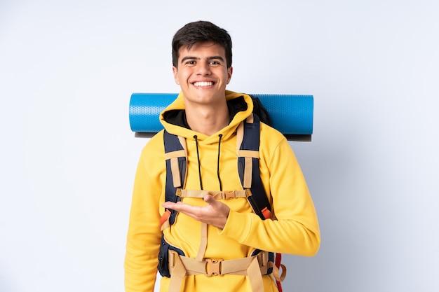 Młody alpinista z dużym plecakiem na białym tle niebieski wyciągając ręce na bok do zapraszania