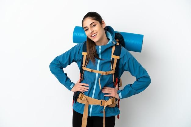Młody alpinista z dużym plecakiem na białym tle pozuje z rękami na biodrach i uśmiecha się