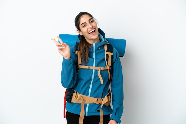 Młody alpinista z dużym plecakiem na białym tle, uśmiechający się i pokazujący znak zwycięstwa