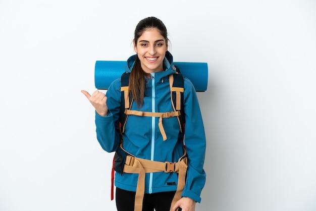 Młody alpinista z dużym plecakiem na białym tle wskazujący na bok, aby zaprezentować produkt