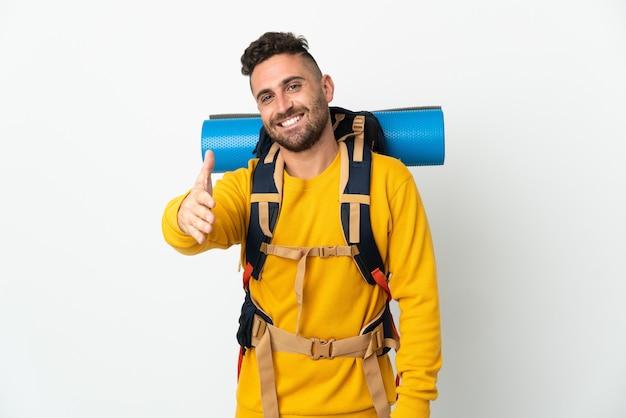 Młody alpinista z dużym plecakiem na odosobnionym tle, ściskając ręce, żeby zamknąć dobrą ofertę good