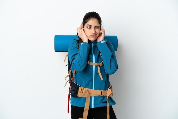 Młody alpinista z dużym plecakiem na odosobnionym tle sfrustrowany i zakrywający uszy