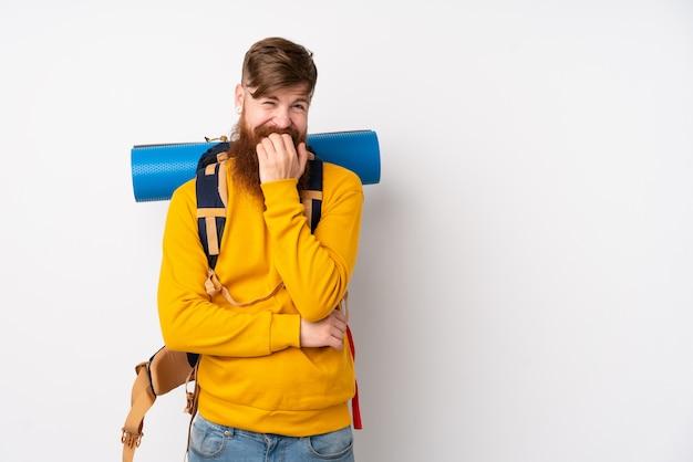 Młody alpinista z dużym plecakiem na pojedyncze białe ściany nerwowe i przestraszony