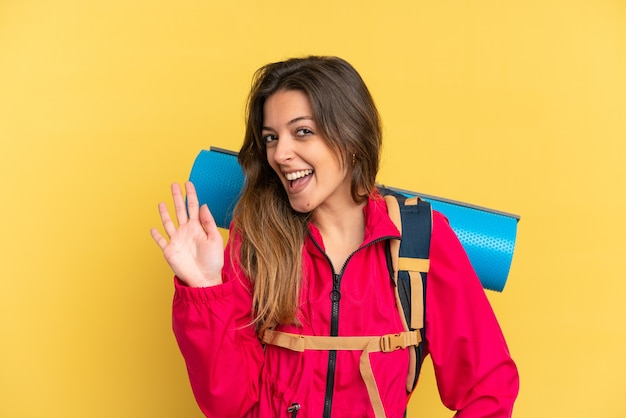 Młody alpinista z dużym plecakiem na żółtym tle pozdrawiający ręką ze szczęśliwym wyrazem twarzy
