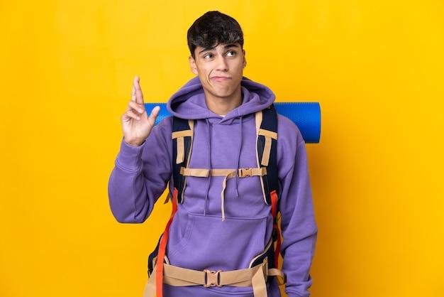 Młody alpinista z dużym plecakiem na żółtym tle z skrzyżowanymi palcami i życzący wszystkiego najlepszego