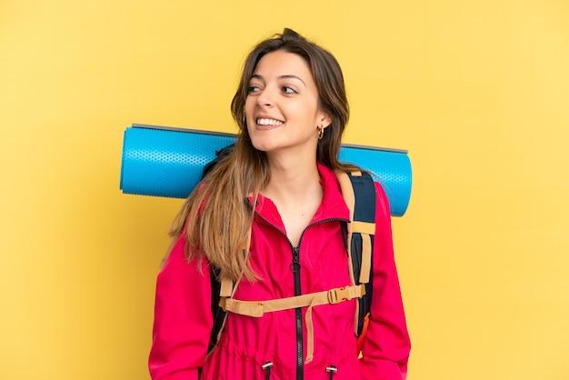 Młody alpinista z dużym plecakiem odizolowanym na żółtym tle patrząc z boku