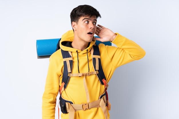 Młody alpinisty mężczyzna słucha coś z dużym plecakiem nad odosobnionym błękitnym tłem