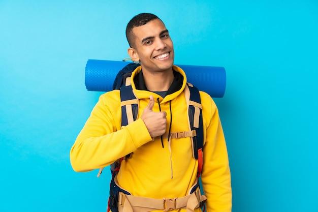 Młody alpinisty mężczyzna z dużym plecakiem nad odosobnioną błękit ścianą daje aprobata gestowi