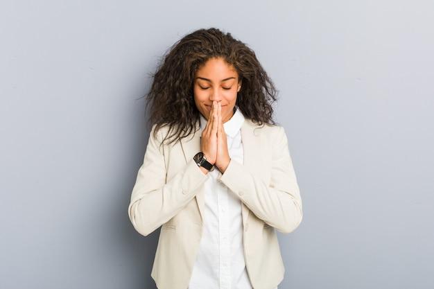 Młody amerykanin afrykańskiego pochodzenia biznesowej kobiety mienia ręki w modlą się blisko usta