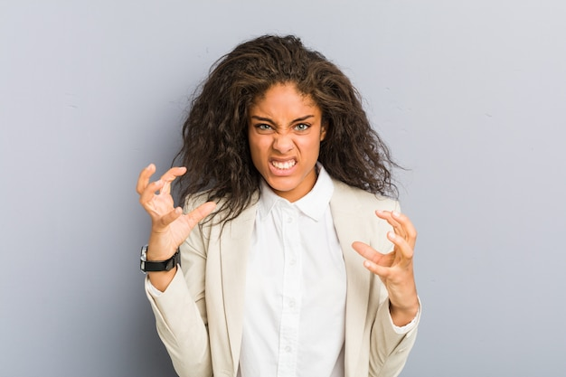 Młody amerykanin afrykańskiego pochodzenia biznesowej kobiety zdenerwowany krzyczy z napiętymi rękami