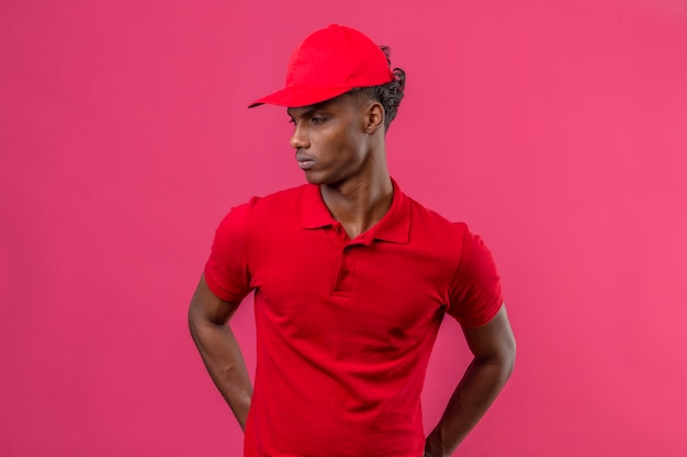 Młody amerykanin afrykańskiego pochodzenia doręczeniowy mężczyzna jest ubranym czerwoną polo koszula i nakrętkę patrzeje daleko od strona z poważną twarzą stoi nad odosobnionymi menchiami