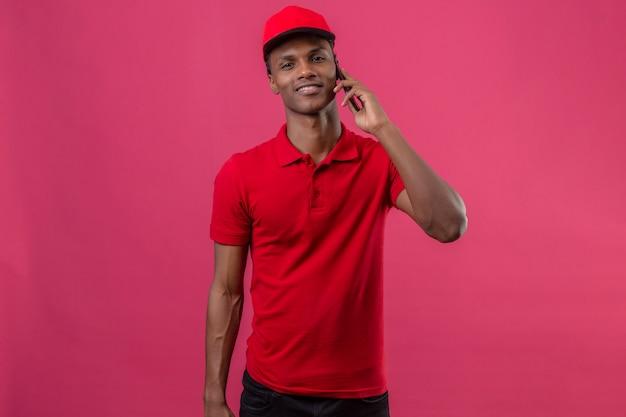 Młody amerykanin afrykańskiego pochodzenia doręczeniowy mężczyzna jest ubranym czerwoną polo koszula i nakrętkę patrzeje ufny i mówi smartphone nad odosobnionym menchiami