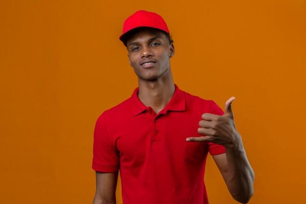Młody amerykanin afrykańskiego pochodzenia doręczeniowy mężczyzna jest ubranym czerwoną polo koszula i nakrętkę patrzeje ufny robi telefonicznemu gestowi dzwoni ja z powrotem podpisuje odosobnionej pomarańcze