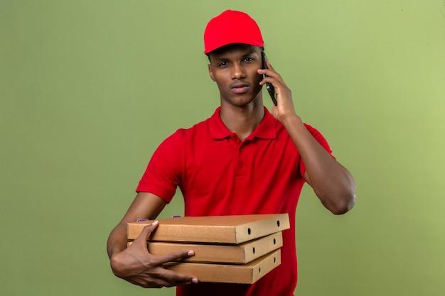 Młody amerykanin afrykańskiego pochodzenia doręczeniowy mężczyzna jest ubranym czerwoną polo koszula i nakrętki przewożenia stertę pizz pudełka podczas gdy mówiący smartphone nad odosobnioną zielenią
