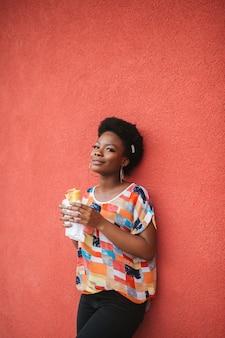 Młody amerykanin afrykańskiego pochodzenia dziewczyny mienia hamburger w ona ręki plenerowe