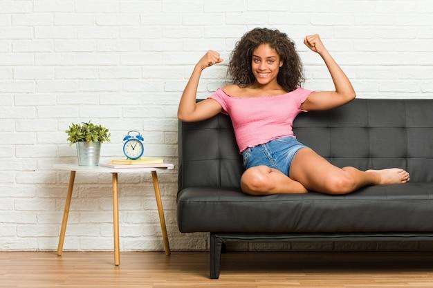 Młody amerykanin afrykańskiego pochodzenia kobiety obsiadanie na kanapie pokazuje siła gest z rękami, symbol kobieca władza