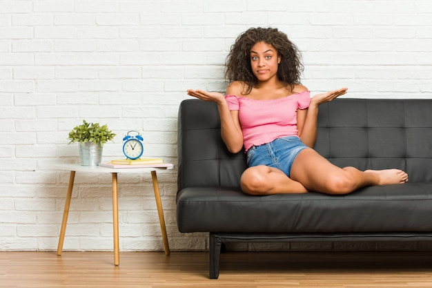 Młody amerykanin afrykańskiego pochodzenia kobiety obsiadanie na kanapie wątpi i wzrusza ramionami ramiona w przesłuchanie gescie.