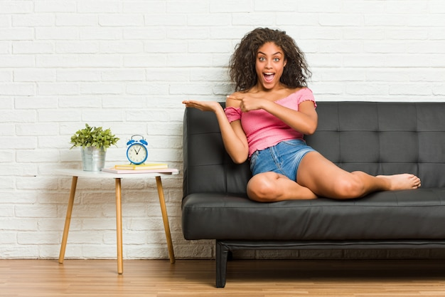 Młody amerykanin afrykańskiego pochodzenia kobiety obsiadanie na kanapie z podnieceniem trzyma odbitkową przestrzeń na palmie.