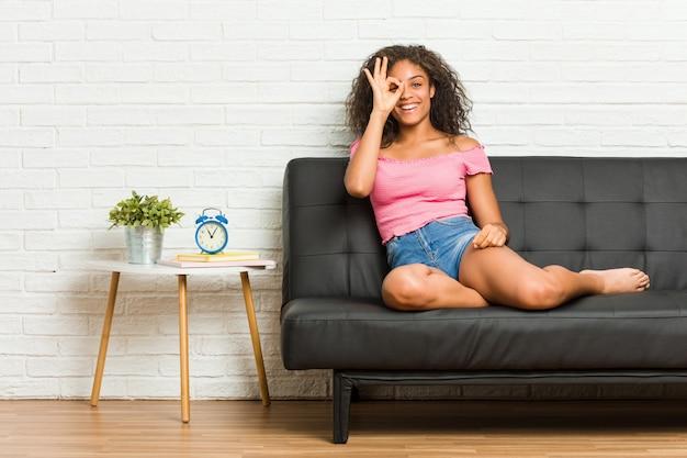 Młody amerykanin afrykańskiego pochodzenia kobiety obsiadanie na kanapie z podnieceniem utrzymuje ok gest na oku.