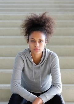 Młody amerykanin afrykańskiego pochodzenia kobiety obsiadanie na krokach z hełmofonami