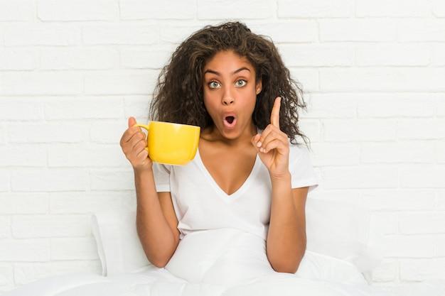Młody amerykanin afrykańskiego pochodzenia kobiety obsiadanie na łóżku trzyma kawowego kubek ma niektóre doskonałego pomysł, pojęcie twórczość.