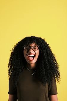 Młody amerykanin afrykańskiego pochodzenia krzyczy z afro fryzurą, okularami i żółtym tłem