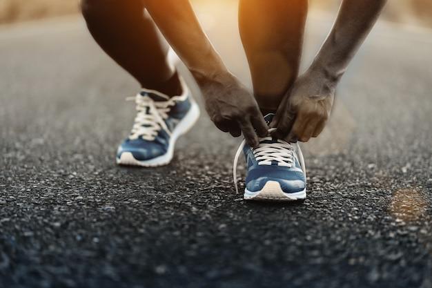 Młody amerykanin afrykańskiego pochodzenia mężczyzna biegacz wiąże sznurowadła na drodze.