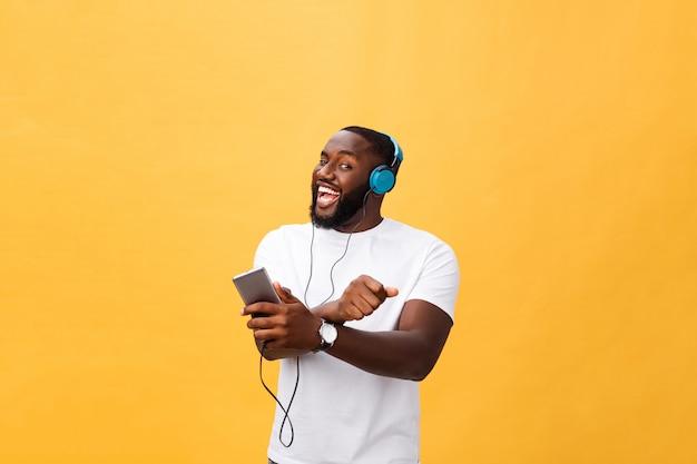 Młody amerykanin afrykańskiego pochodzenia mężczyzna jest ubranym hełmofon i cieszy się muzykę nad żółtego złota tłem