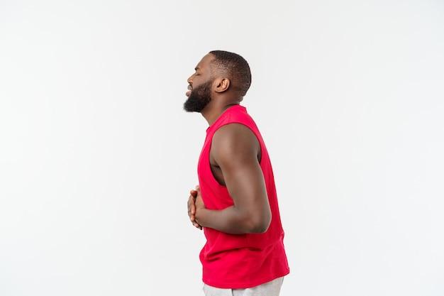Młody amerykanin afrykańskiego pochodzenia mężczyzna jest ubranym sport odzież z ręką na żołądku ponieważ mdłości, bolesna choroba czuje się źle.