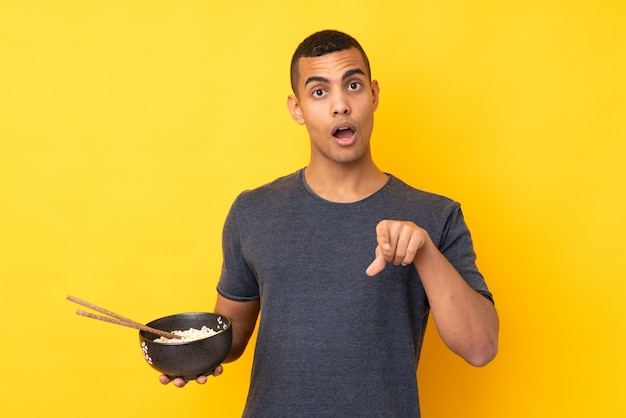 Młody amerykanin afrykańskiego pochodzenia mężczyzna nad odosobnioną kolor żółty ścianą zaskakującą i wskazującą przód podczas gdy trzymający puchar kluski z pałeczkami