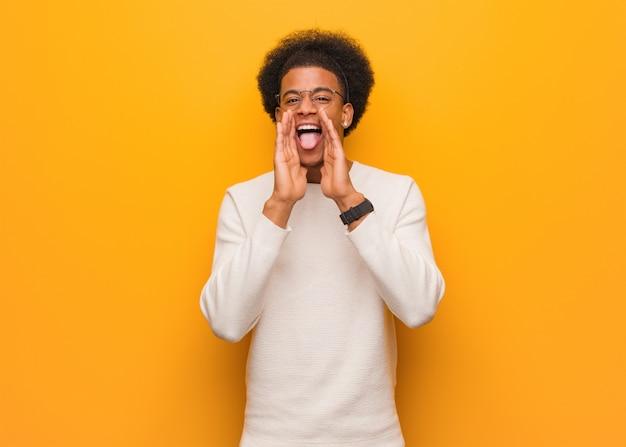 Młody amerykanin afrykańskiego pochodzenia mężczyzna nad pomarańczową ścianą krzyczy coś szczęśliwego z przodu