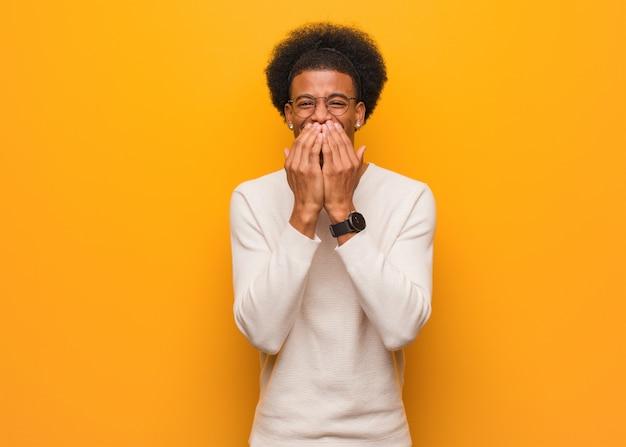 Młody amerykanin afrykańskiego pochodzenia mężczyzna nad pomarańczową ścianą śmia się z czegoś, zakrywający usta rękami