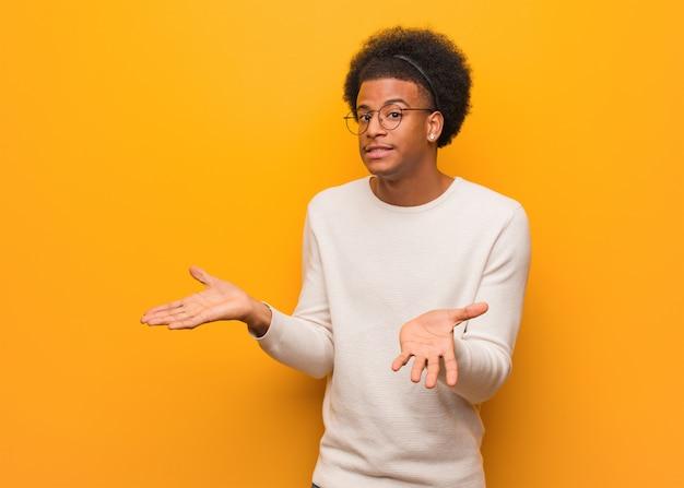 Młody amerykanin afrykańskiego pochodzenia mężczyzna nad pomarańczową ścianą zmieszaną i wątpliwą