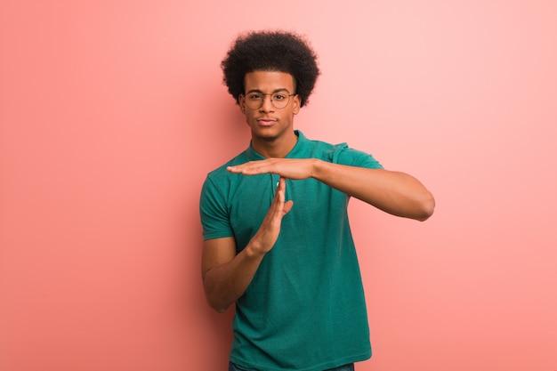 Młody amerykanin afrykańskiego pochodzenia mężczyzna nad różową ścianą robi limitu czasu gestowi