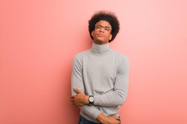 Młody amerykanin afrykańskiego pochodzenia mężczyzna nad różową ścianą zmęczoną i znudzoną