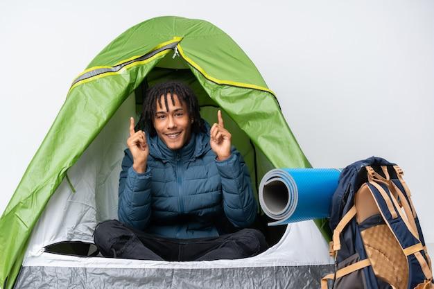 Młody amerykanin afrykańskiego pochodzenia mężczyzna wśrodku campingowego zielonego namiotu wskazuje w górę doskonałego pomysłu