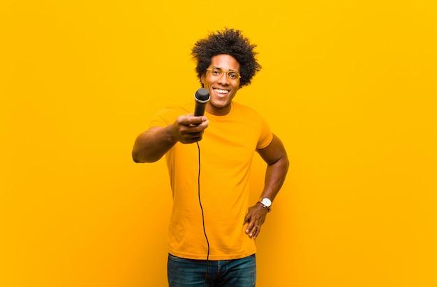 Młody amerykanin afrykańskiego pochodzenia mężczyzna z mikrofonu śpiewem