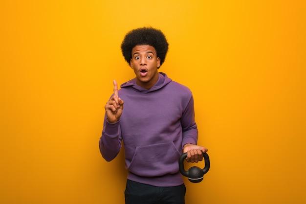 Młody amerykanin afrykańskiego pochodzenia sprawności fizycznej mężczyzna trzyma dumbbell ma doskonałego pomysł, twórczość