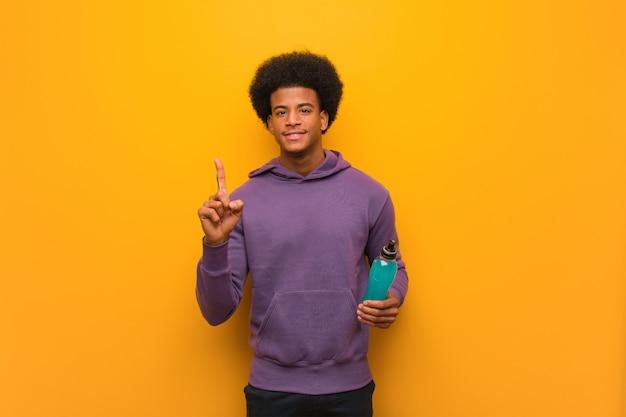 Młody amerykanin afrykańskiego pochodzenia sprawności fizycznej mężczyzna trzyma energetycznego napój pokazuje liczbę jeden