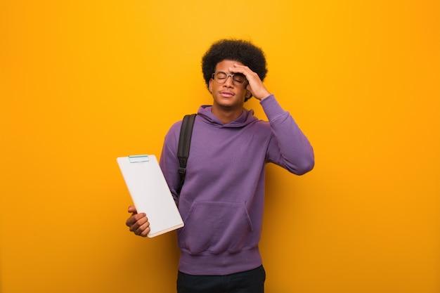 Młody amerykanin afrykańskiego pochodzenia studencki mężczyzna trzyma schowek martwiącego się i przytłaczającego