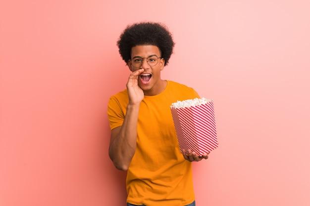 Młody amerykanin afrykańskiego pochodzenia trzyma popkornowego wiadro krzyczy coś szczęśliwego przód