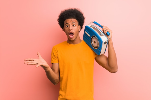 Młody amerykanin afrykańskiego pochodzenia trzyma rocznika radio świętuje zwycięstwo lub sukces