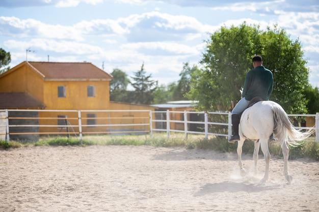Młody amerykanin afrykańskiego pochodzenia w przypadkowym stroju jedzie białego konia na piaskowatej ziemi na rancho