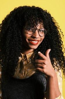 Młody amerykanin afrykańskiego pochodzenia z afro fryzurą, okularami i żółtym tłem