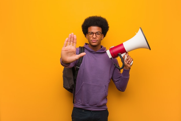Młody amerykanina afrykańskiego pochodzenia mężczyzna holdinga megafon stawia rękę w przodzie